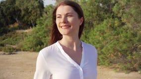 少妇走在绿色公园的画象愉快微笑 吹她的在慢动作的风头发 股票视频