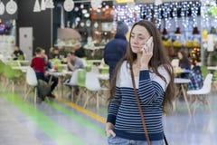 少妇走在购物中心和谈话在一个白色智能手机 免版税库存图片
