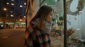 少妇走通过与装饰和花的一个商店窗口在晚上 影视素材