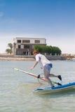 少妇跌下风帆冲浪的委员会在埃及, Hurgha 免版税库存照片