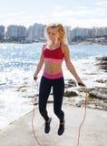 少妇跳绳在海岸,室外 图库摄影