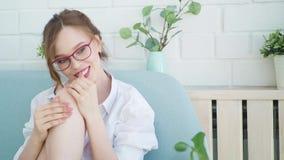 少妇身体关心在舒适客厅 应用在她的手上的美丽的女孩奶油剥皮坐在长沙发 股票视频
