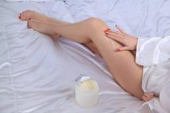 少妇身体关心奶油是应用的在腿 库存图片