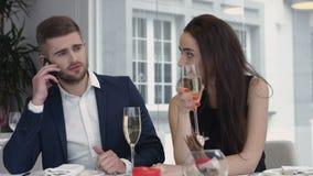 少妇迄今乏味,当有她的男朋友在手机的企业细胞,供以人员繁忙使用他们巧妙的电话在时 免版税库存照片