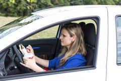 少妇运作的和饮用的咖啡,当驾驶时 免版税库存图片