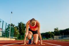 少妇运动员在准备好的开始状态开始在跑马场的种族 库存照片
