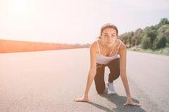 少妇运动员在准备好的开始状态开始种族 女性短跑选手准备好体育在跑马场行使 图库摄影