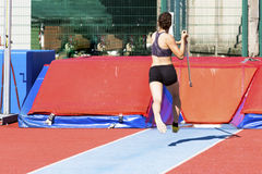 少妇运动员执行跳高撑竿跳高 免版税库存图片
