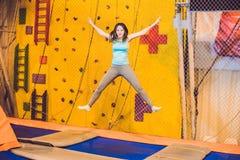 少妇运动员跳跃在一张绷床在健身的公园 库存图片