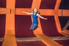 少妇运动员跳跃在一张绷床在健身的公园 免版税库存图片