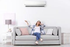 少妇运行的空调器,当坐时 免版税库存照片