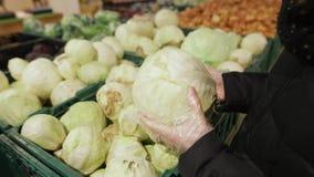 少妇选择在货架的圆白菜 Ð一个可爱的少妇的手¡ loseup有一棵菜的在它 股票录像