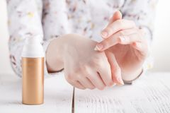 少妇递应用润湿的奶油于她的皮肤 图库摄影