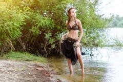 少妇部族美国风格的舞蹈家 女孩跳舞和摆在海滩沙子佩带的肚皮舞服装 种族 库存照片