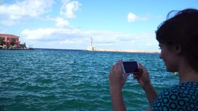 少妇采取照片在欧洲城市用途智能手机的一座灯塔 股票视频