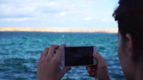 少妇采取照片在欧洲城市用途智能手机的一座灯塔 股票录像