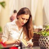 少妇阅读书在咖啡馆的桌上 免版税库存照片