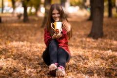 少妇饮料热的茶在秋天公园 库存照片