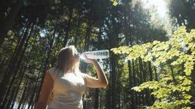 少妇饮用水户外在晴朗的公园或森林 股票视频