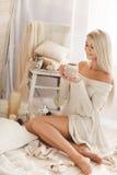 少妇饮用的咖啡在家在他的屋子里 库存图片
