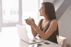 少妇饮用的咖啡,当与膝上型计算机一起使用在桌上时 库存照片