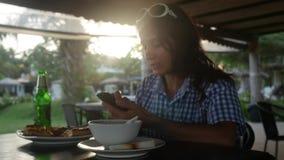 少妇饮用的啤酒吃晚餐和与她的手机的送消息在一个室外咖啡馆在日落期间和 股票录像