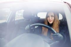 少妇驱动一辆汽车在冬天 免版税库存照片