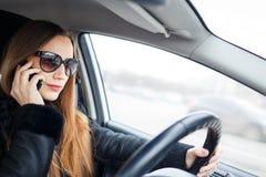 少妇驱动一辆汽车在冬天 免版税图库摄影