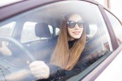 少妇驱动一辆汽车在冬天 免版税库存图片