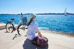 少妇骑马在海附近的城市自行车 库存照片