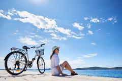 少妇骑马在海附近的城市自行车 免版税库存照片