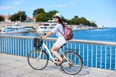 少妇骑马在海附近的城市自行车 免版税库存图片