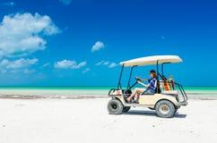 少妇骑马在热带海滩的高尔夫车 图库摄影