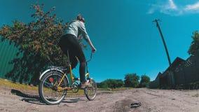 少妇骑马沿一条农村路的葡萄酒自行车在村庄 股票视频