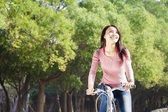 少妇骑马自行车在公园 免版税库存图片