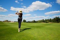 少妇高尔夫球运动员,后面看法画象  免版税库存图片