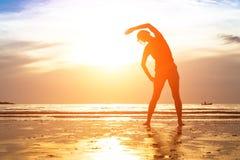 少妇,在海滩的锻炼在日落 库存照片