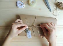 少妇,缝合包裹交付的小企业所有者一个小包 礼物wraping的想法 库存图片