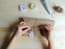 少妇,缝合包裹交付的小企业所有者一个小包 礼物wraping的想法 免版税库存照片