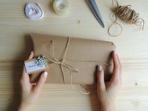 少妇,缝合包裹交付的小企业所有者一个小包 礼物wraping的想法 图库摄影