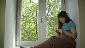 少妇从与编织针的蓝色毛线编织坐基石 影视素材