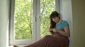 少妇从与编织针的蓝色毛线编织坐基石 股票视频