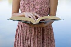 少妇读书圣经在自然公园 库存照片