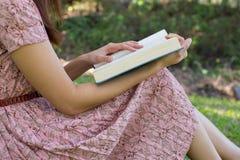 少妇读书圣经在自然公园 免版税库存照片