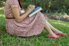 少妇读书圣经在自然公园 免版税库存图片