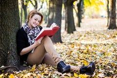 少妇读书在秋天公园 免版税图库摄影