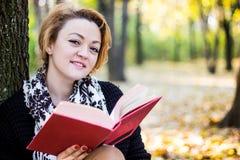 少妇读书在秋天公园 库存照片