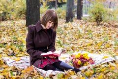 少妇读书在秋天公园 免版税库存图片
