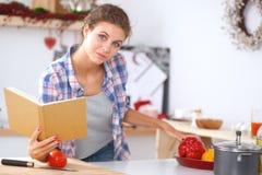少妇读书菜谱在厨房里, 免版税库存图片