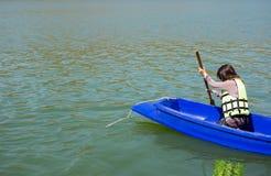 少妇今后装备救生衣划船 她不看 库存照片